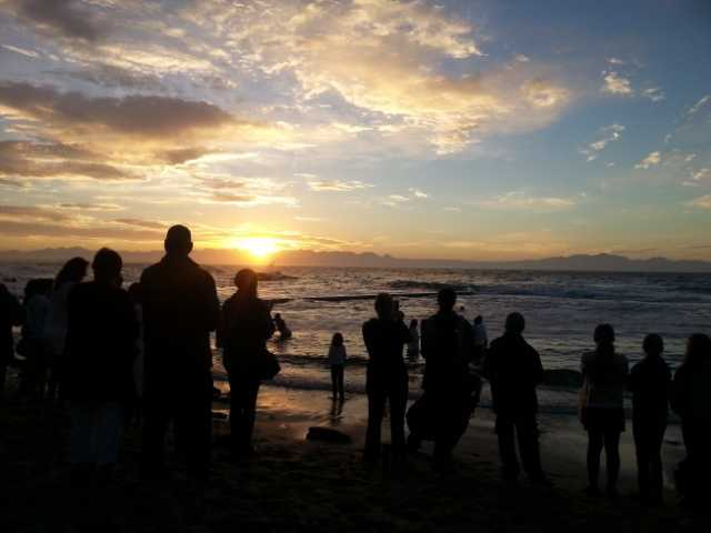 People watching sunrise baptism at St James Beach Cape Town